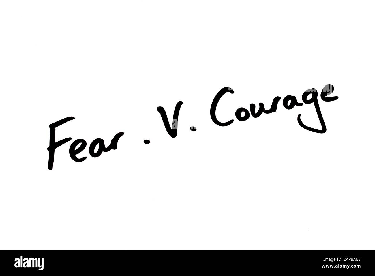Close-up of Fear .v. Courage handwritten on a white background. Stock Photo