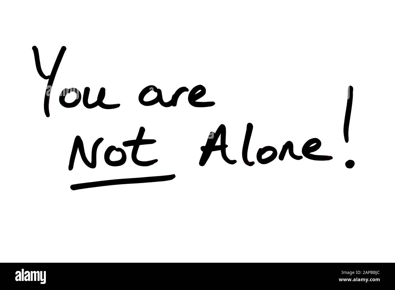 You are NOT Alone! handwritten on a white background. Stock Photo