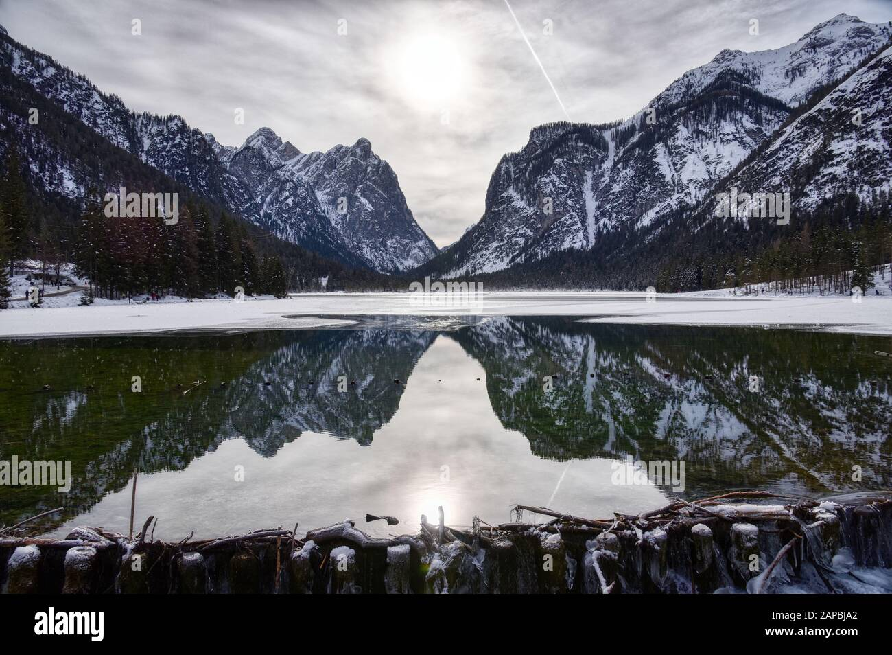 The mountains of the valley are reflected by the cold waters of Lake Dobbiaco Stock Photo