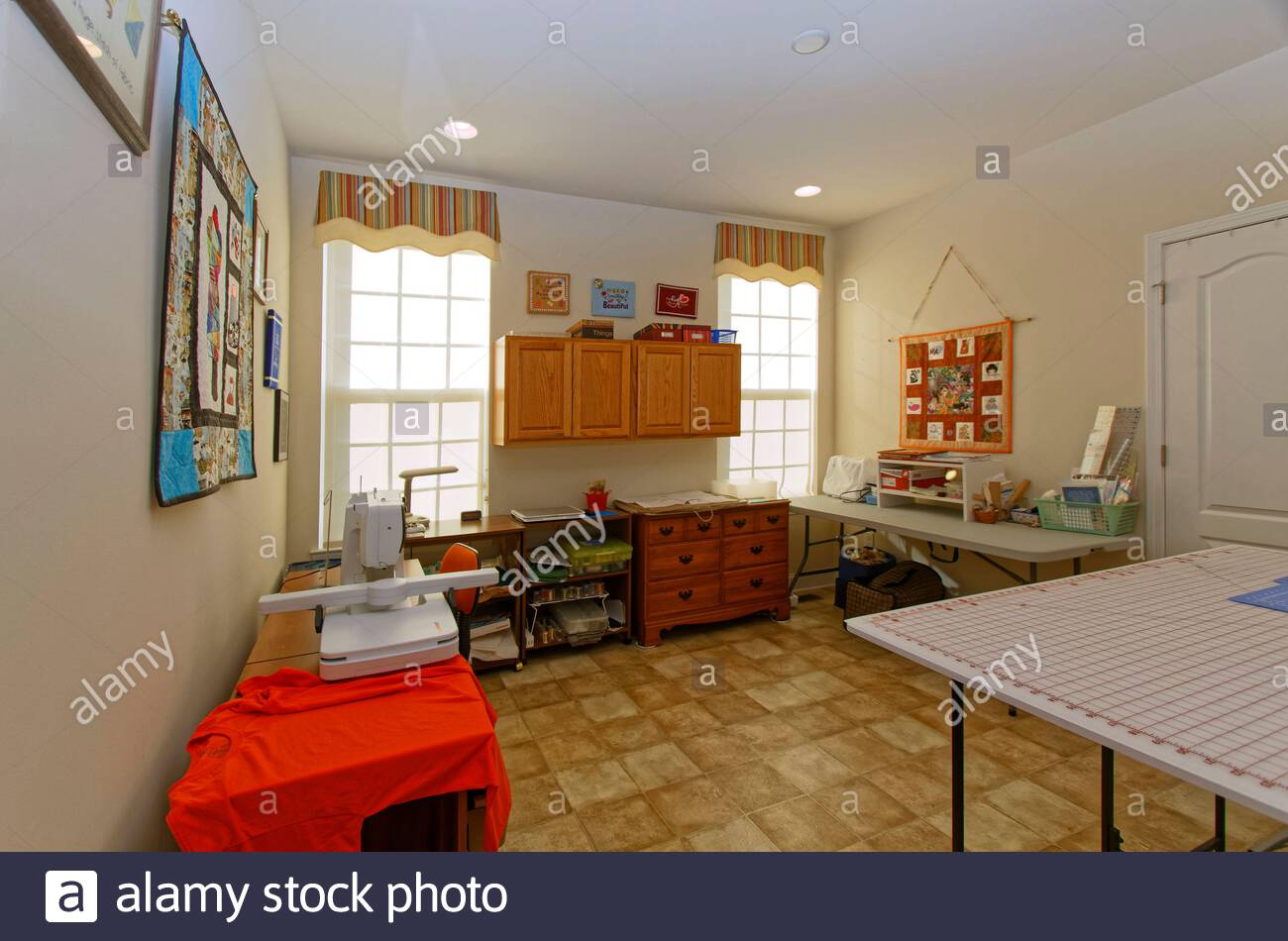 sewing room, house, bright light, 2 windows, fiber art wall decorations, cabinets, cutting table, sewing machine, work table, supplies, horizontal; PR Stock Photo