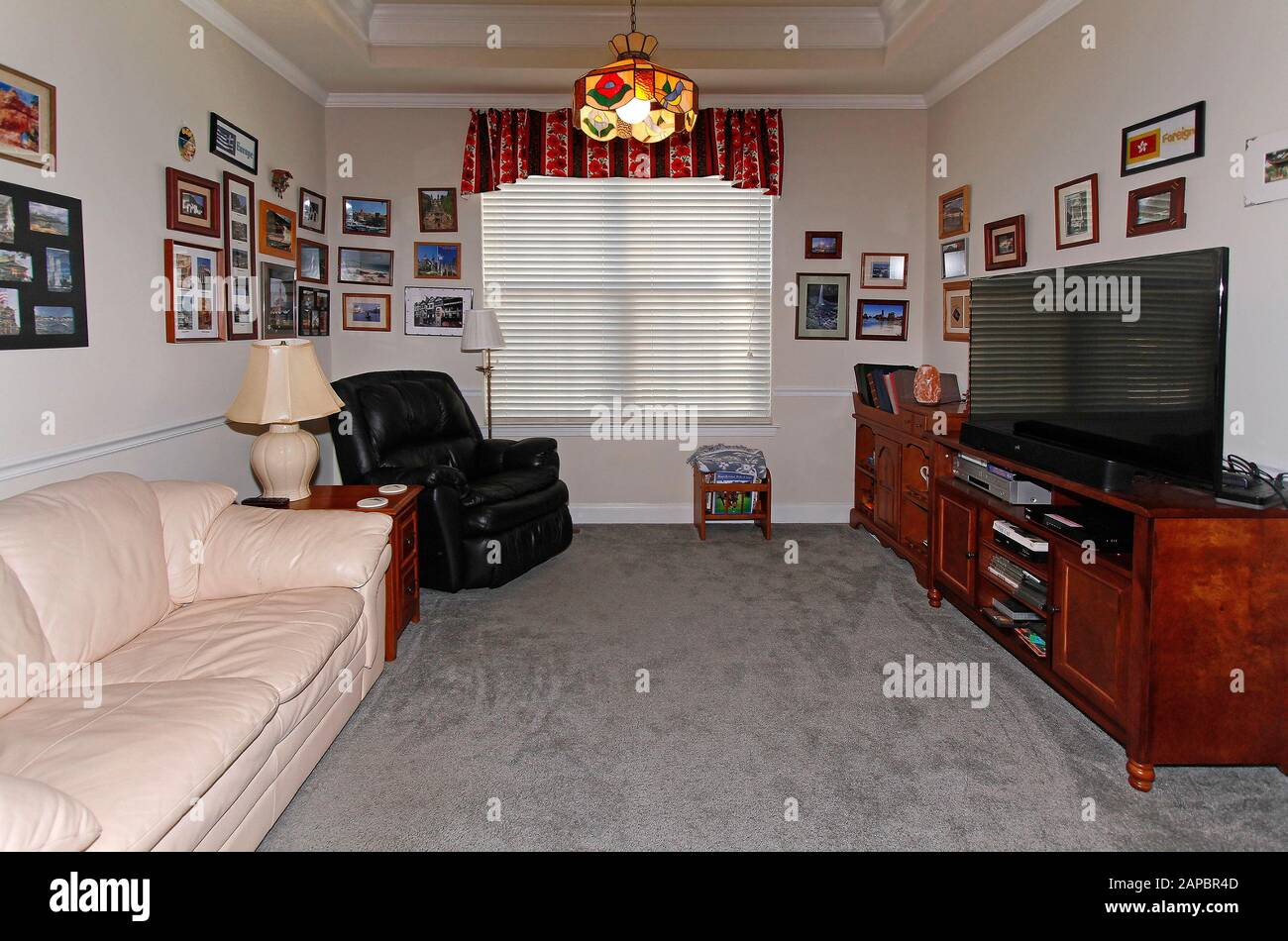 den, TV room, house, stained glass chandelier, leather furniture, sofa, recliner, many photos, cozy, large window, shades closed, wood cabinets, coffe Stock Photo