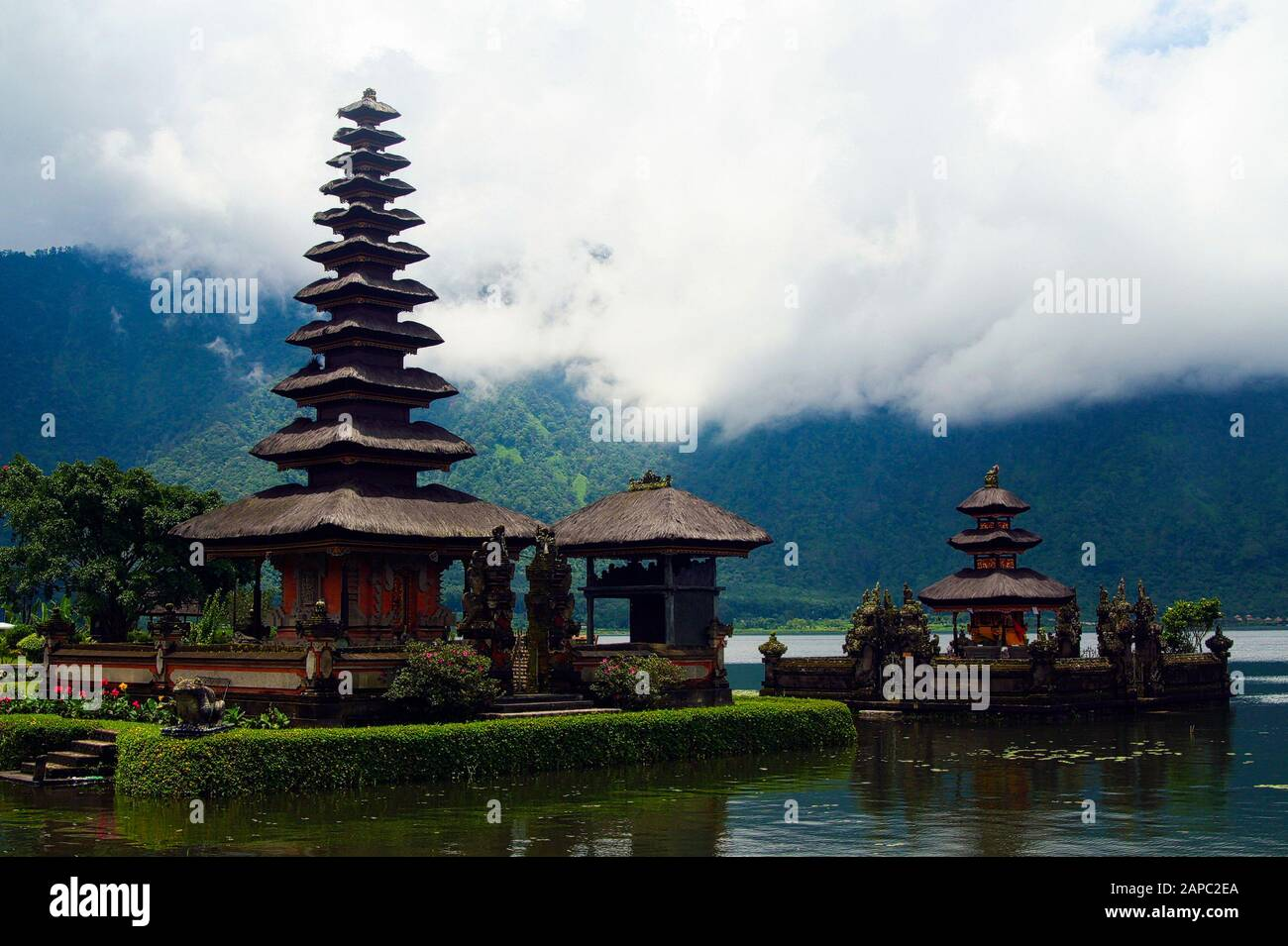 Moody atmosphere with low hanging clouds fog over lake at Pura Ulun Danu Batur temple on Bratan lake - Bali Stock Photo
