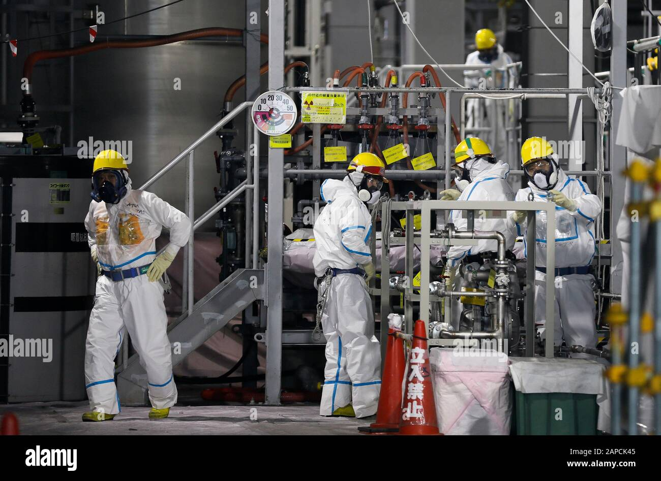 January 22, 2020, Okuma, Fukushima, Japan: Fully covered workers check water processing system ALPS(Multi-nuclide retrieval equipment) where process contaminated water to store in tanks at ALPS' house of  tsunami-devastated Tokyo Electric Power Company (TEPCO) Fukushima Daiichi Nuclear Power Plant in Okuma town, Fukushima Prefecture, 22 January 2020 after transferring to new tanks. The storage tanks including water processed in the ALPS will be full around summer of 2022, TEPCO has told. Japanese government will need to decide soon how manage the processed water still including tritium.  (Cred Stock Photo