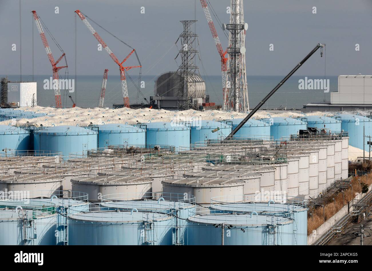 January 22, 2020, Okuma, Fukushima, Japan: Workers demolish old storage tanks included water processed in ALPS(Multi-nuclide retrieval equipment) at  tsunami-devastated Tokyo Electric Power Company (TEPCO) Fukushima Daiichi Nuclear Power Plant in Okuma town, Fukushima Prefecture, 22 January 2020 after transferring to new tanks. The storage tanks including water processed in the ALPS will be full around summer of 2022, TEPCO has told. Japanese government will need to decide soon how manage the processed water still including tritium. The Unit 2 reactor house in left rear, the Unit 3 reactor hou Stock Photo