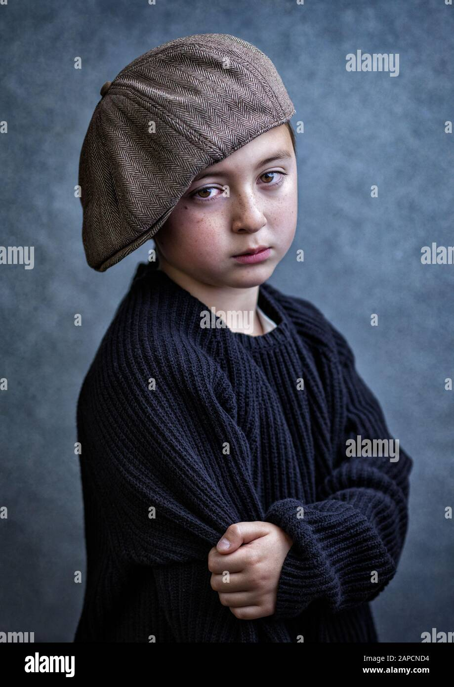 Handsome multi-racial Asian Caucasian little juvenile delinquent boy wearing a black knit wool sweater and a brown tweed newsboy cap our gang Stock Photo
