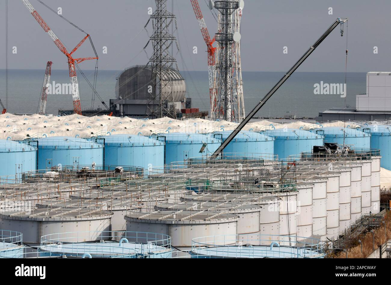 Okuma, Fukushima, Japan. 22nd Jan, 2020. Workers demolish old storage tanks included water processed in ALPS(Multi-nuclide retrieval equipment) at tsunami-devastated Tokyo Electric Power Company (TEPCO) Fukushima Daiichi Nuclear Power Plant in Okuma town, Fukushima Prefecture, 22 January 2020 after transferring to new tanks. The storage tanks including water processed in the ALPS will be full around summer of 2022, TEPCO has told. Japanese government will need to decide soon how manage the processed water still including tritium. The Unit 3 reactor house in left rear and the Unit 4 reactor Stock Photo