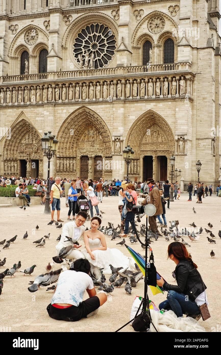 Street photograph of a Bridal Shoot with pigeons, statue of Charlemagne et ses Leudes at Cathédrale Notre-Dame de Paris. Stock Photo