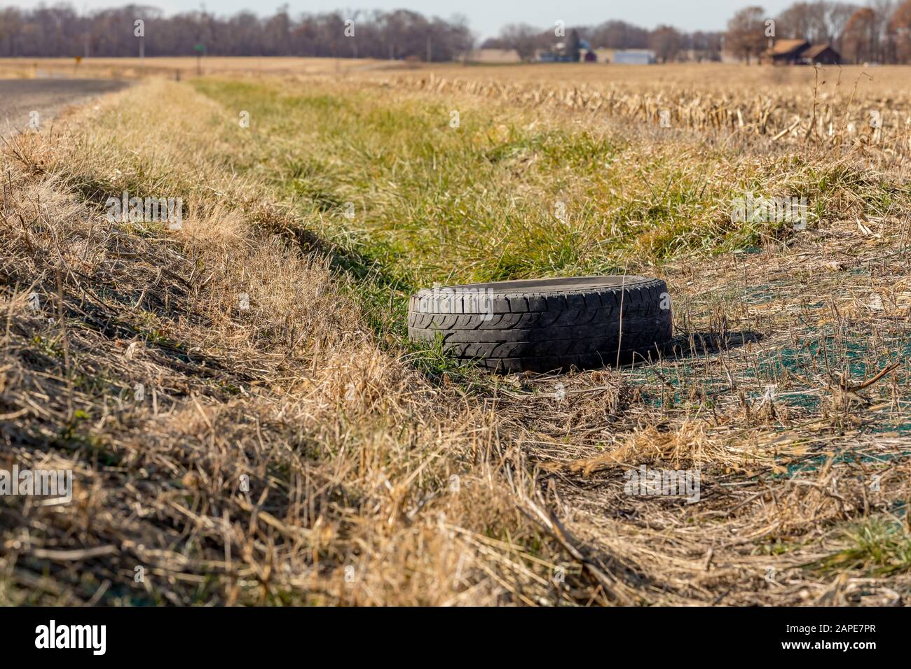 Old black rubber tire dumped in ditch along rural road. Concept of pollution, environmental damage and recycling Stock Photo