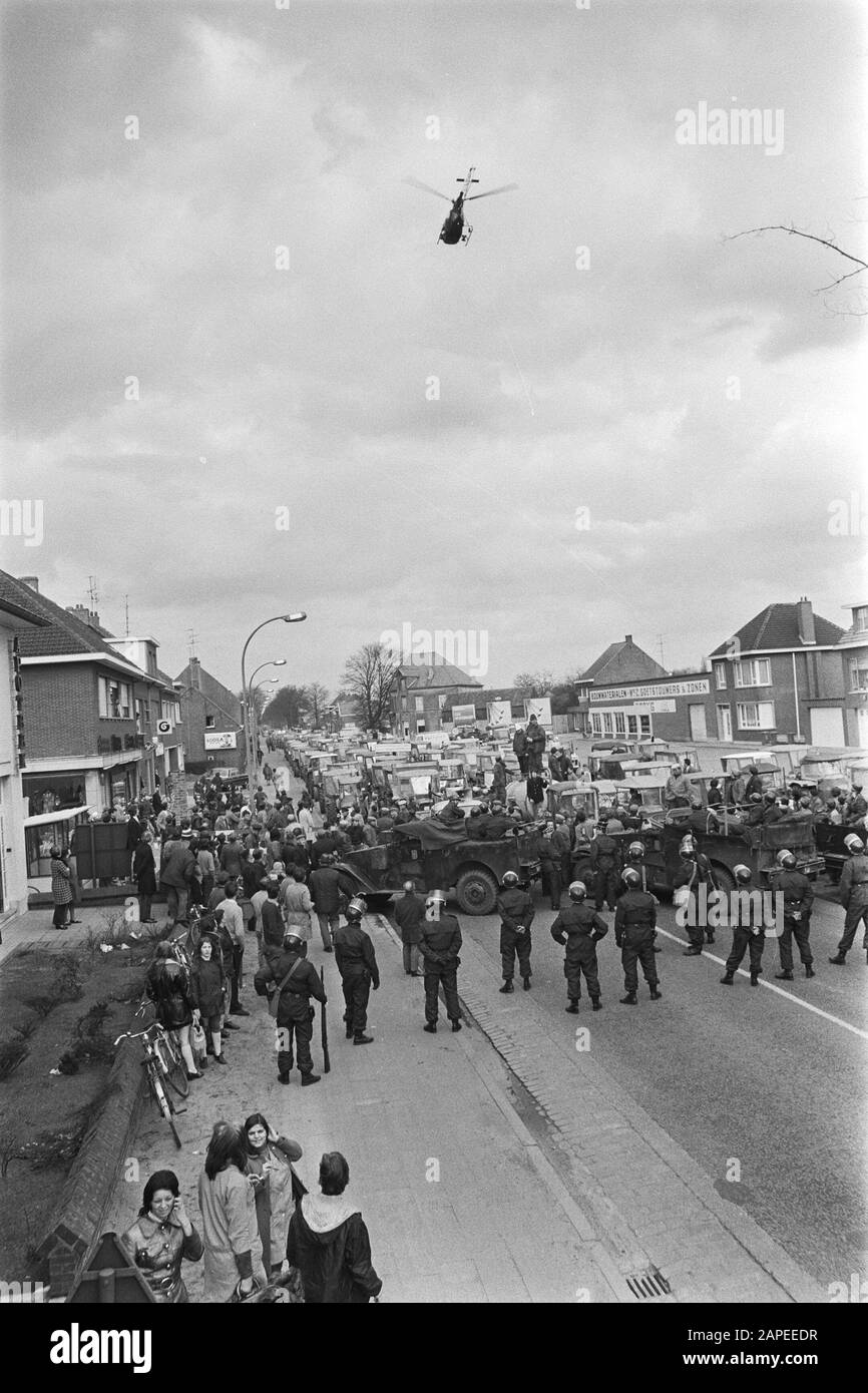 Demonstration of Belgian farmers with tractors on the road of the Netherlands Description: Belgian Rijkswacht blocks the road, above it a helicopter Date: 19 March 1971 Location: Belgium Keywords: demonstrations, farmers, helicopters, police officers, tractors Stock Photo
