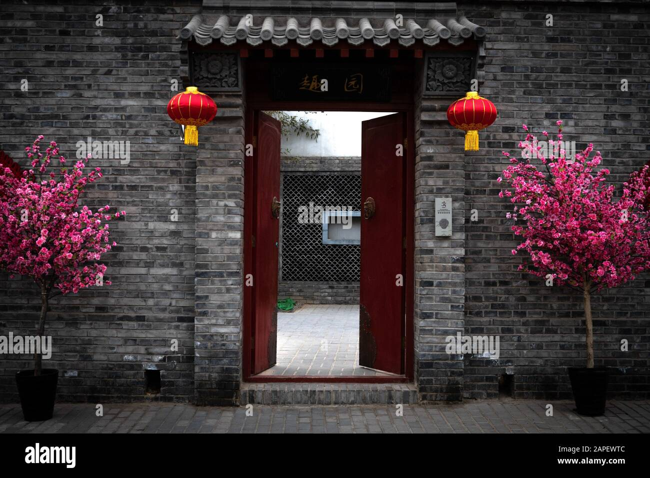 Red door and gate giving entrance to a private courtyard and a dwelling house in a hutong alley in Beijing, China. Decorated for the Chinese New Year Stock Photo