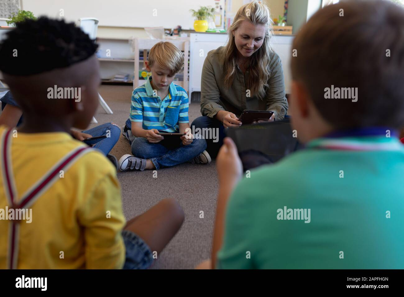 Female school teacher sitting cross legged on the floor in a circle with a group of schoolchildren Stock Photo