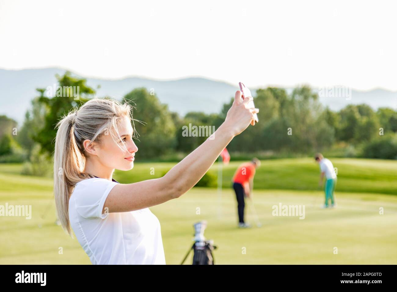 Woman Taking Selfie On Golf Course Friends Playing Golf In Background Stock Photo Alamy