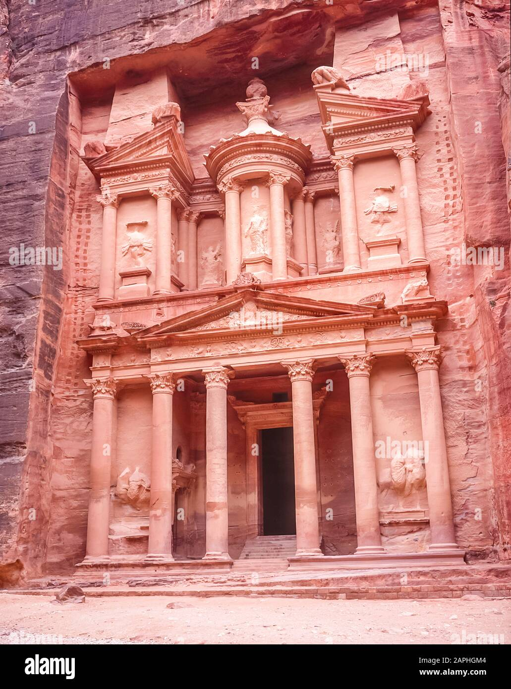 Jordan. The Treasury Building, the Khazaneh at the entrance to the World famous UNESCO World Heritage Site of the Nabatean and Roman  ruins and relics at the desert town of Petra much used as a motion picture film set such as Indiana Jones Temple of Doom, now a very popular tourist attraction. Of interest is that the carvings of of people perhaps Gods have no faces or legs. These were hacked or shot off during early Islamic times as images of Infidels Stock Photo