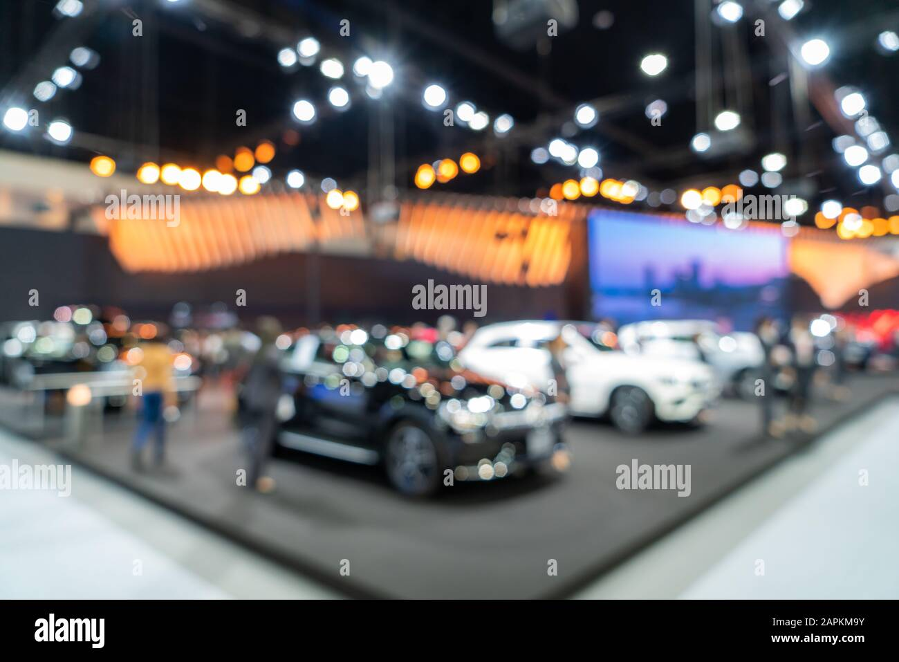 Blurred background of new cars displayed in luxury showroom with light bokeh, motor show event. Stock Photo