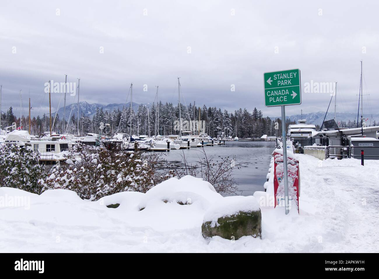 """Vancouver, Canada - January 15,2019: View of road signs """"Stanley Park"""" and """"Canada Place"""" in Coal Harbour with frozen dock in the background Stock Photo"""
