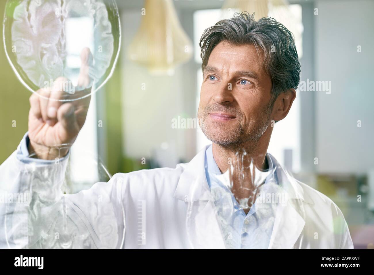Doctor using futuristic touchscreen with cat scan Stock Photo