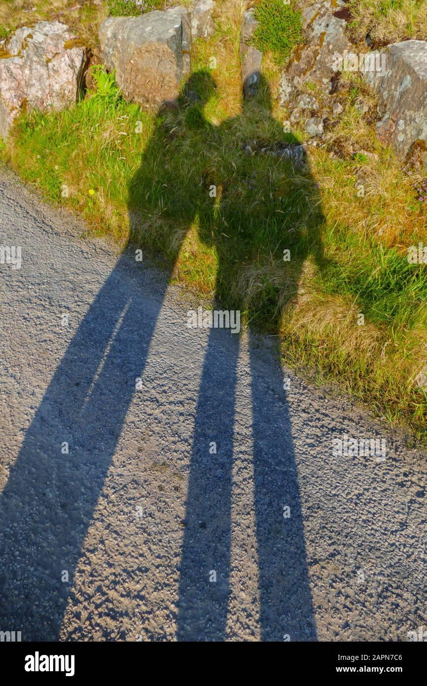 Ein Mann und eine Frau werfen einen langen Schatten auf Straße und Wiese Stock Photo