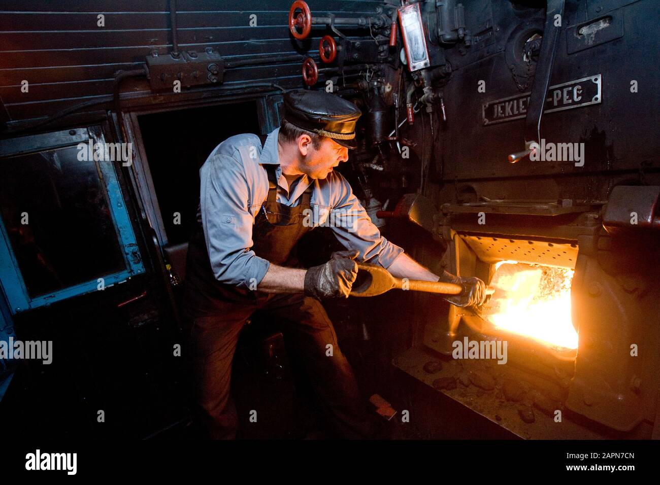 Most na Soči, Slovenia, October 4, 2008: A stoker shovels coal into the furnace of a 1944 Henschel & Son German steam engine that pulls an old museum train on the Bohinj railway line (Transalpina) built from 1900 to 1906 as the shortest connection of the Austro-Hungarian Empire with the Adriatic Sea in Trieste (Italy). Stock Photo