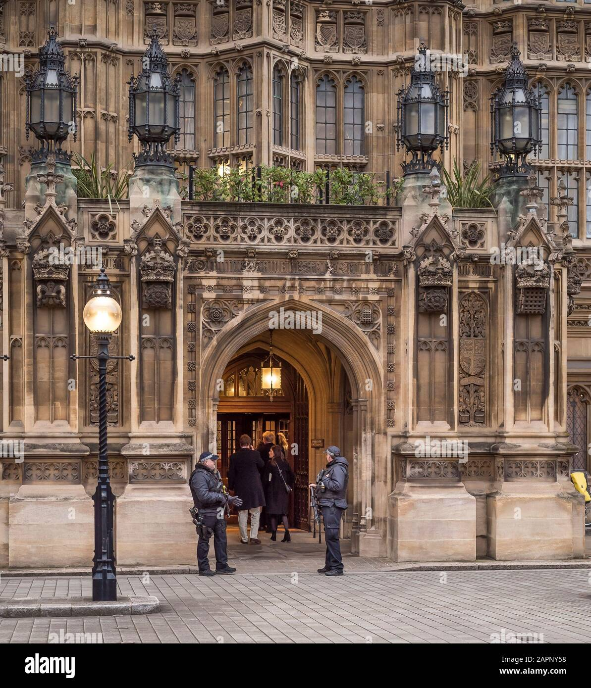 Armed security guards standing outside Houses of Parliament entrance as visitors enter (rear view), Westminster, London UK. Police guarding government. Stock Photo