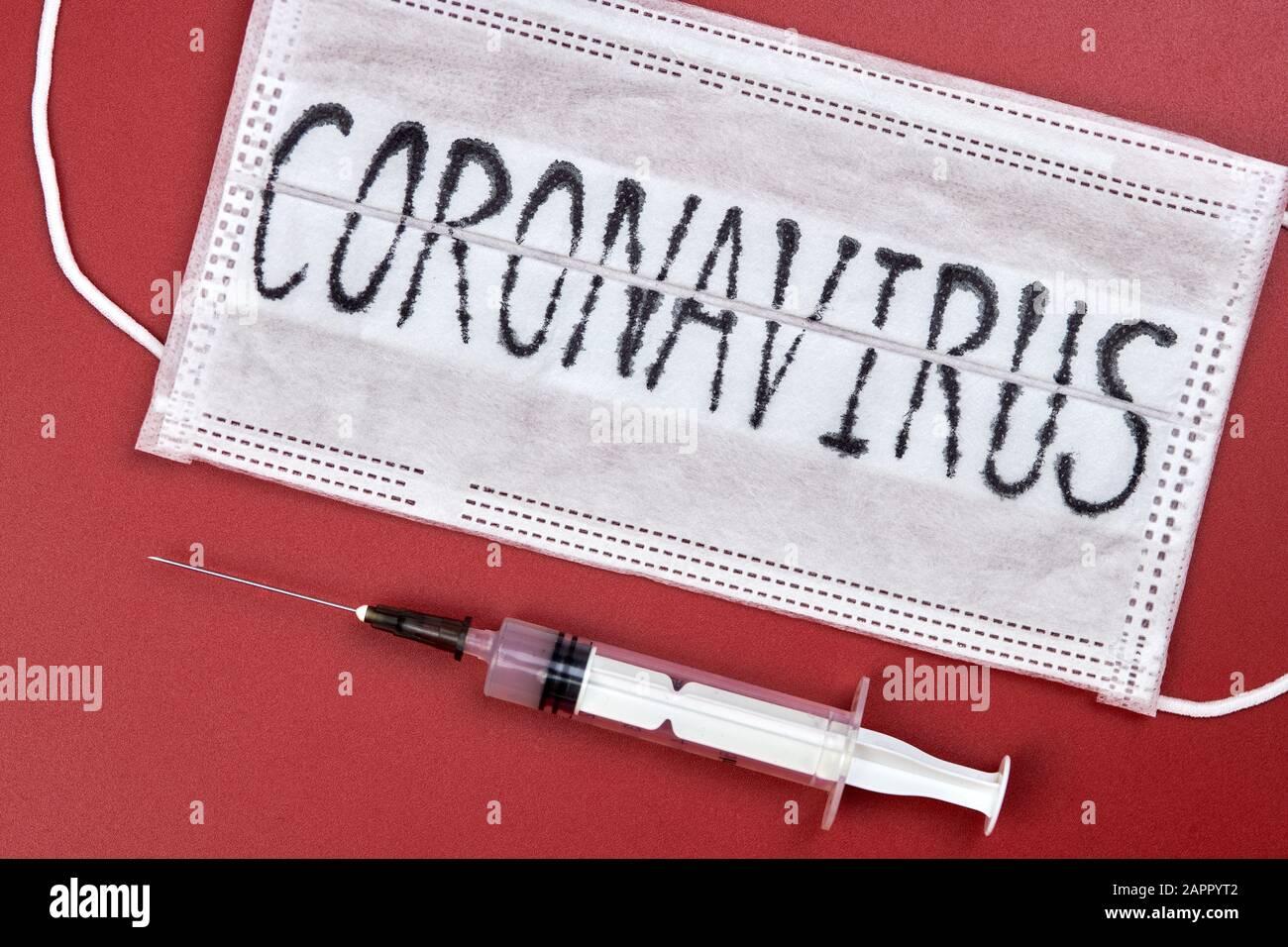 Novel coronavirus - 2019-nCoV, WUHAN virus concept. Surgical mask protective mask with CORONAVIRUS text. Chinese coronavirus outbreak. Red background. Stock Photo