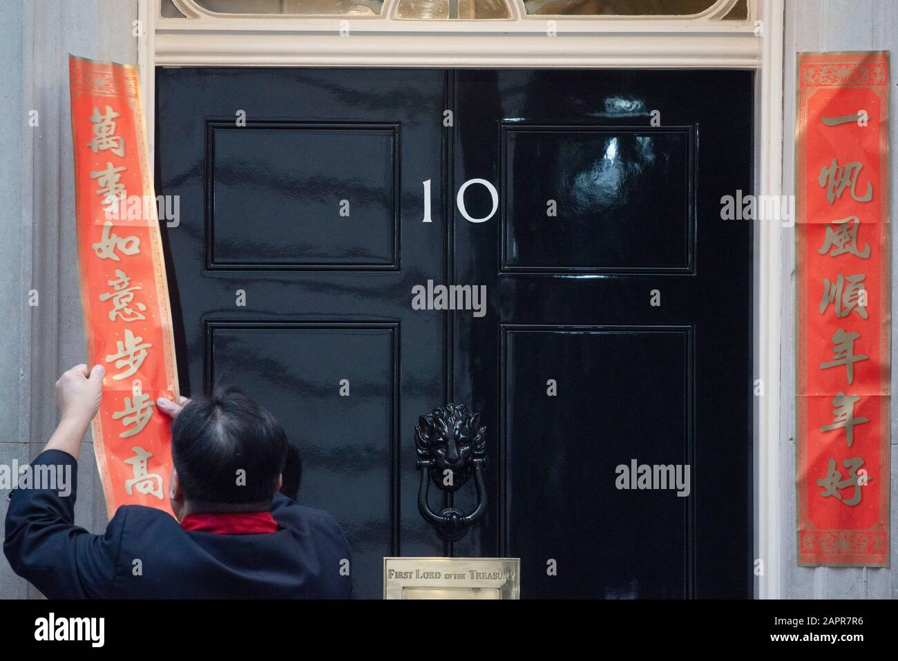 London, UK. 24th Jan, 2020. A man pastes couplets outside 10 Downing Street in London, Britain, Jan. 24, 2020, to celebrate the Chinese Lunar New Year. Credit: Ray Tang/Xinhua/Alamy Live News Stock Photo