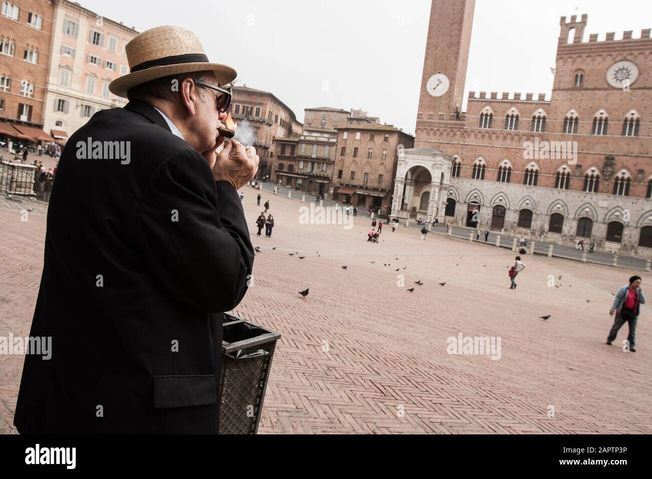 Siena, Italy, October 27, 2008: A man lights a cigar in the Piazza del Campo in Siena, Italy. Stock Photo