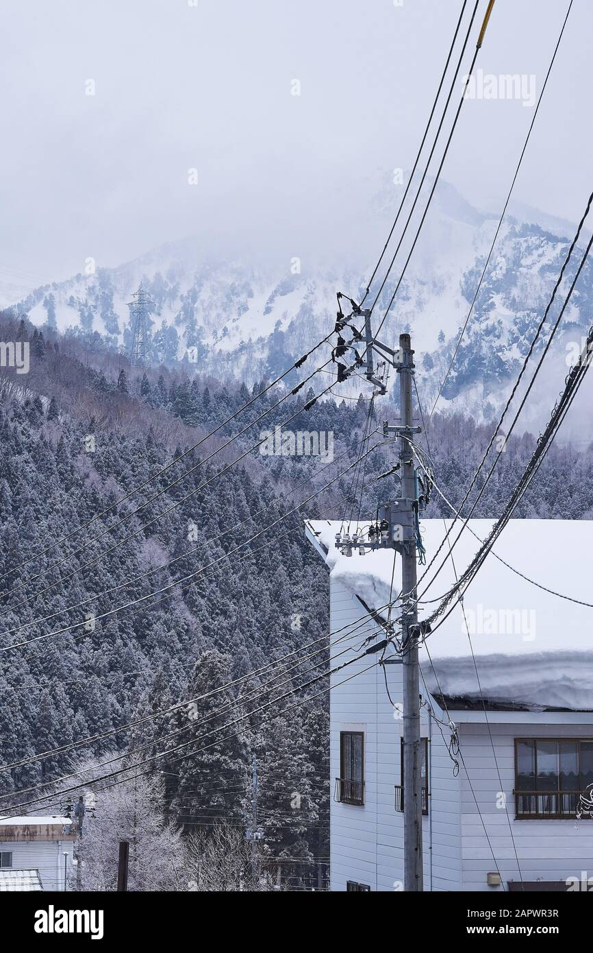 Power lines and snow covered building in the foreground, with snowy trees and mountains in the background. Stock Photo