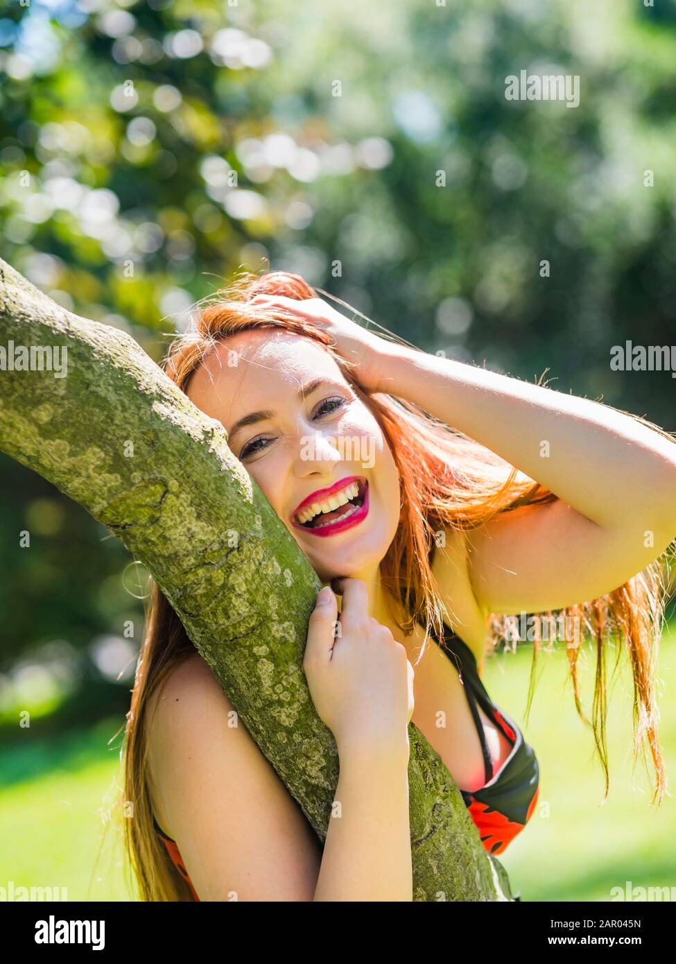 Very happy and laughing portrait inclined on tree in park hand holding head Red-haired redhaired redhair hair Ginger beguiled Stock Photo