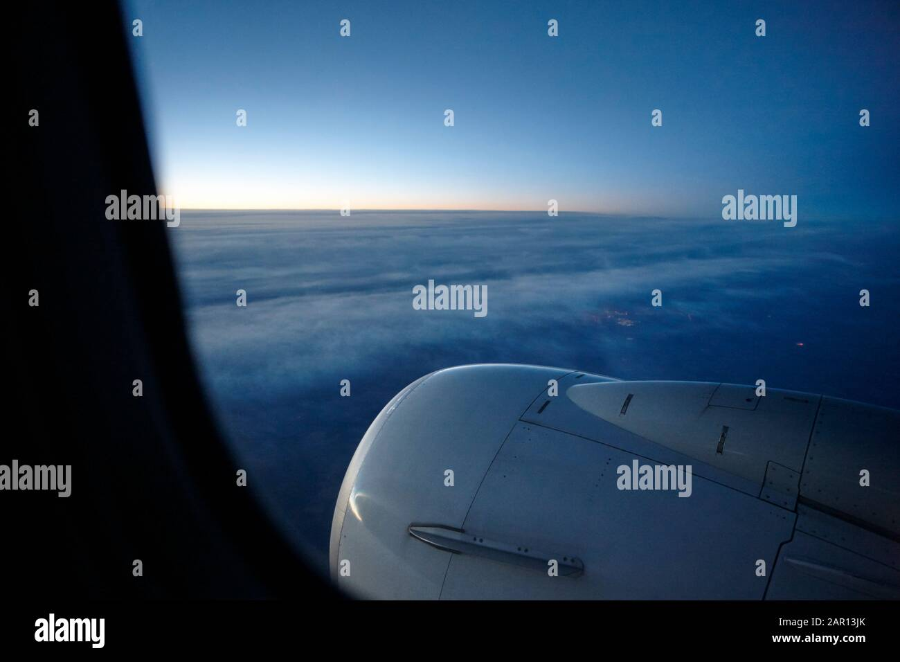 looking out of aircraft window at sunrise flying east on a red-eye flight over north american continent early morning Stock Photo
