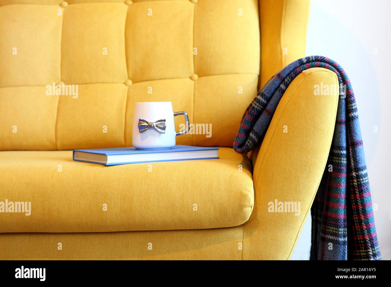 Cup of tea and blue book on yellow coach with blanket. Still life details in home interior of living room. Cozy home interior, home comfort concept Stock Photo