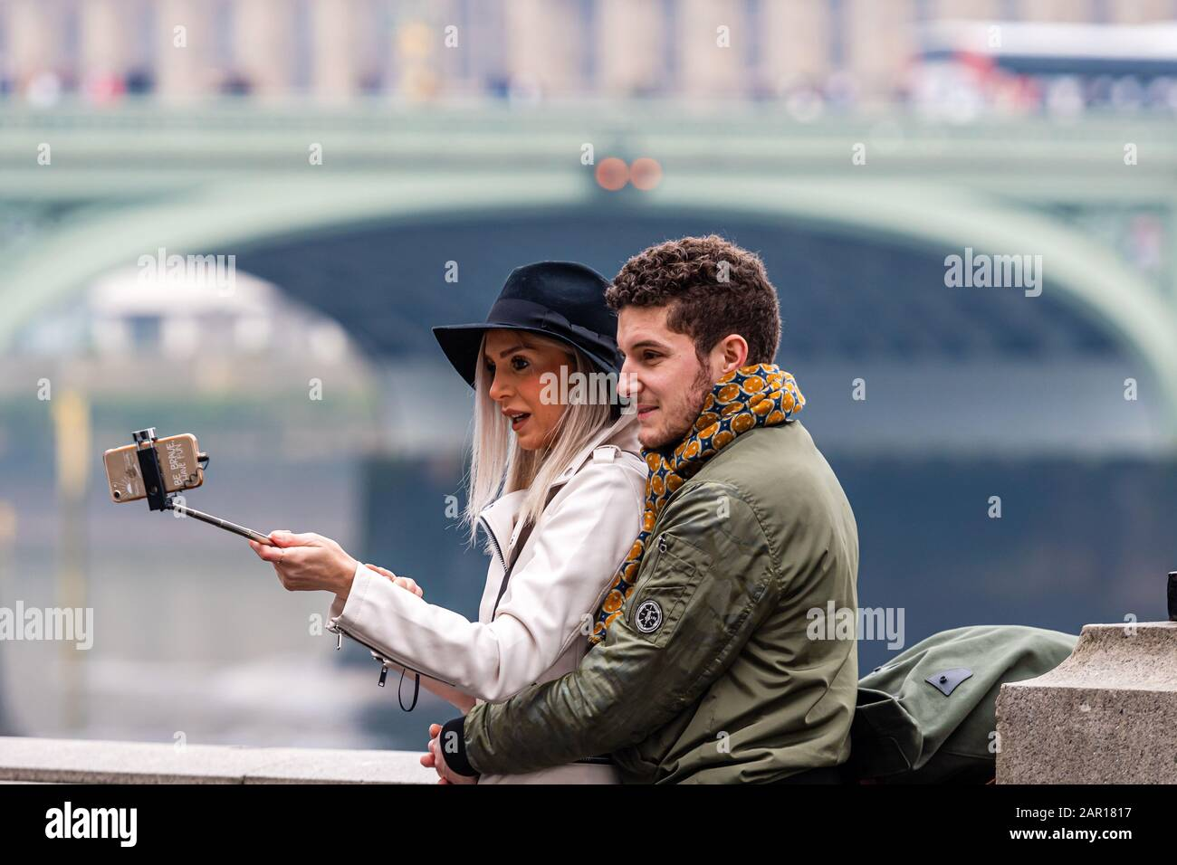 London, UK - January 1, 2020: A couple of young people take selfies with a London skyline in the background Stock Photo
