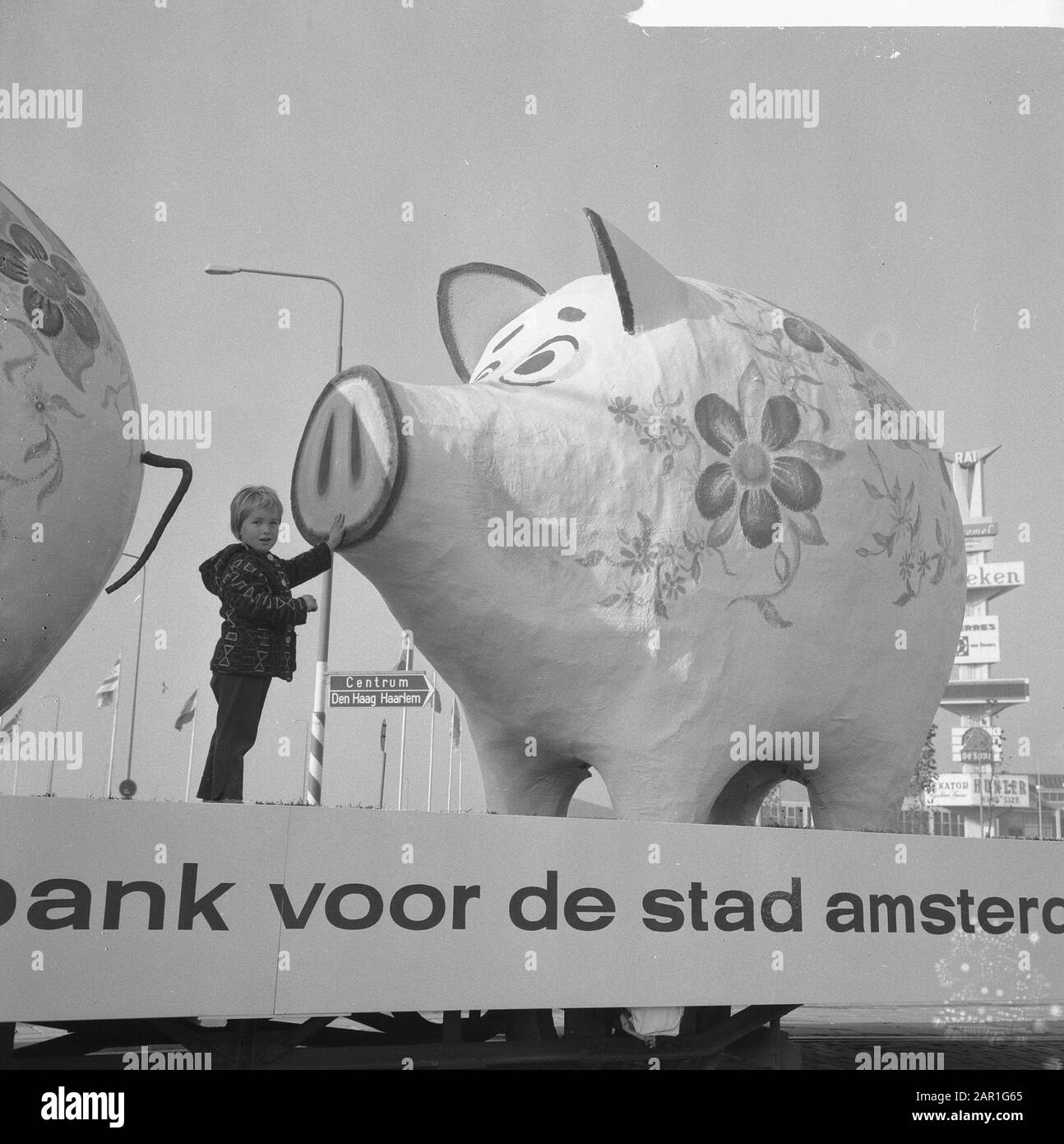 World Savings Day Action Two Giant Piggy Banks On Trailer With The Text Savings Bank For The City Of Amsterdam Child Standing Next To The Piggy Bank Date 25 October 1965 Location