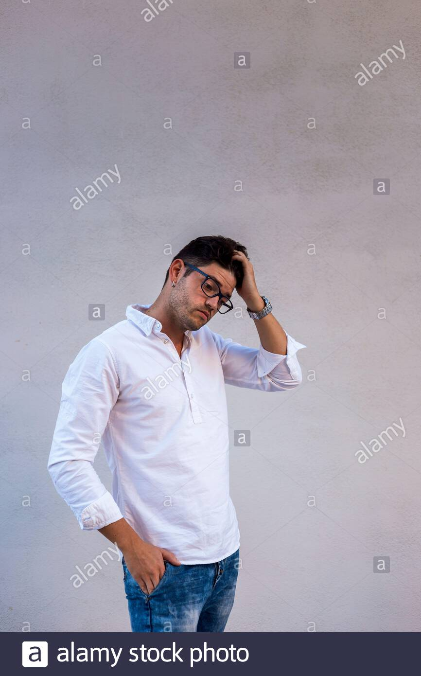 Doubtful young man wearing glasses and white shirt touches his hair. Light background Stock Photo