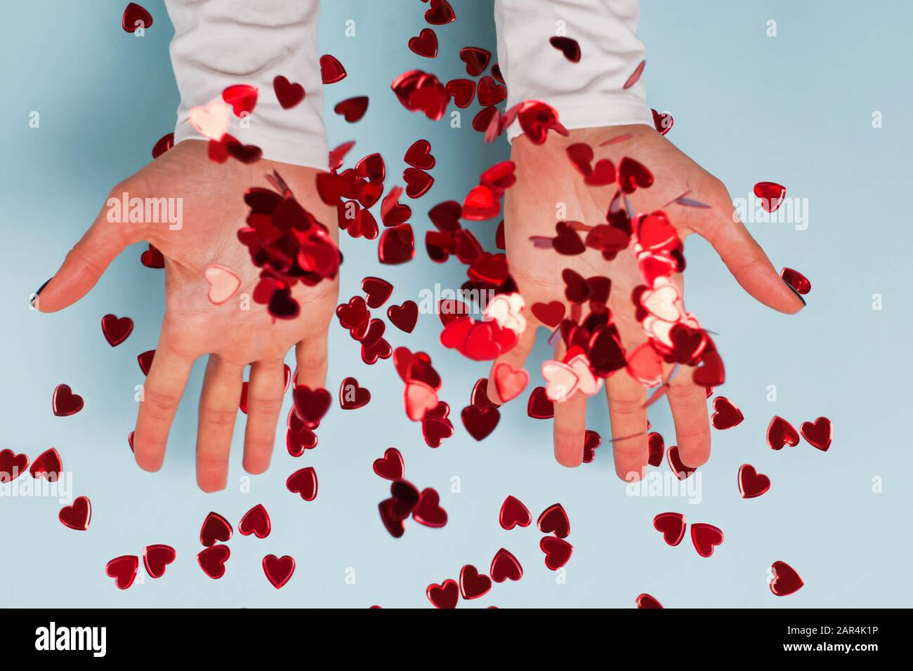 Woman's hands throwing up red heart shaped glitter confetti on ...