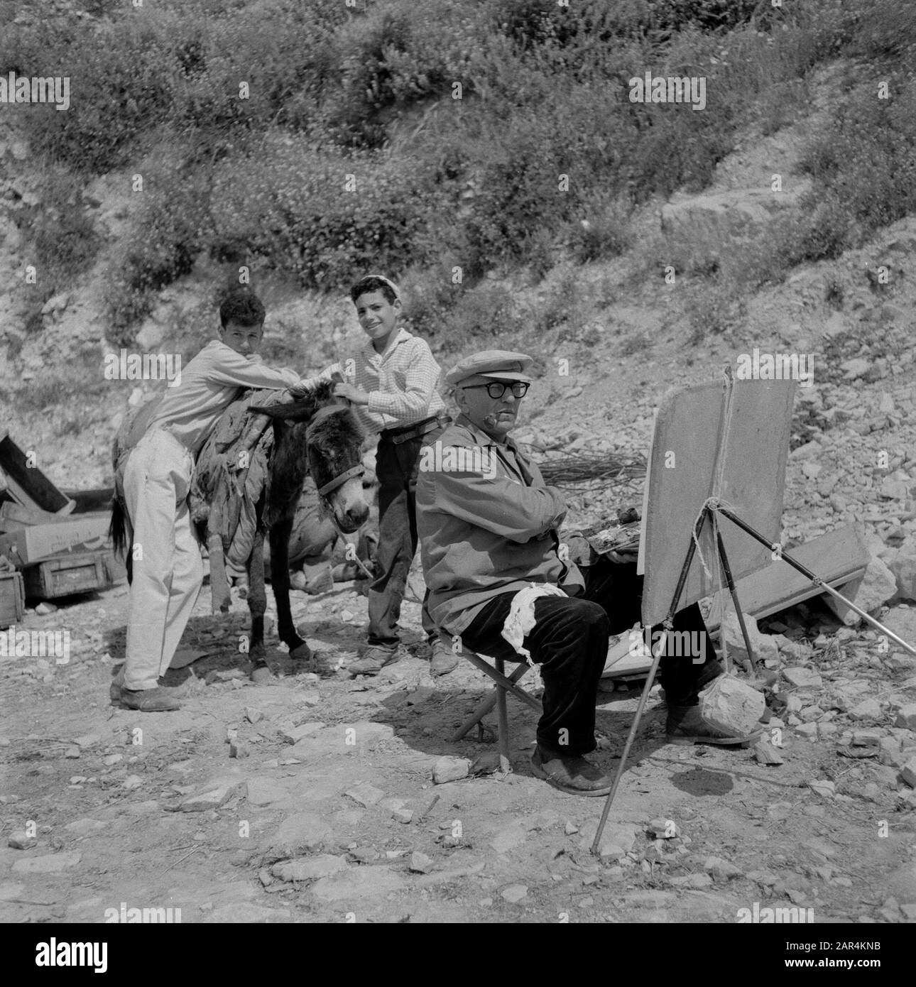 An artist at work on the street in Safad (Safed). Two little boys with a donkey watch Date: undated Location: Israel, Safad, Safed Keywords: visual artists, donkeys, children, street images Stock Photo