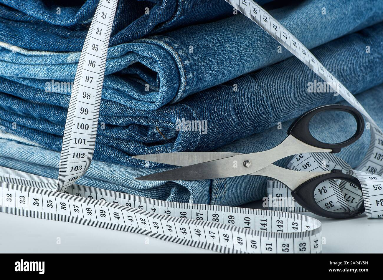 Blue cotton jeans folded on a table with a tape measure and scissors on a white isolated background. Stock Photo