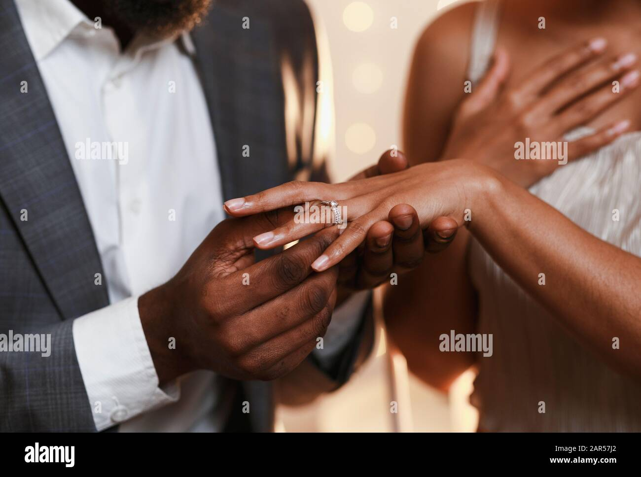 Close up of afro man putting ring on woman finger Stock Photo