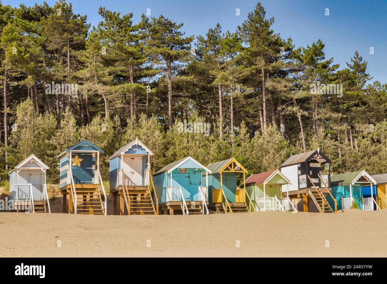29 June 2019: Wells-Next-The-Sea, Norfolk, England, UK - Bathing huts on the beach, pine trees behind. Stock Photo
