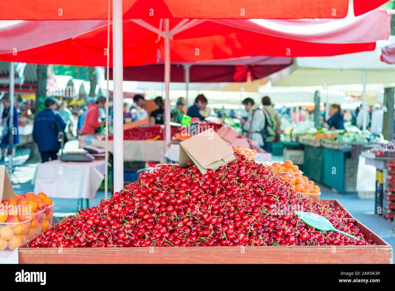 Fruitstand at open market selling fresh cherries. Stock Photo