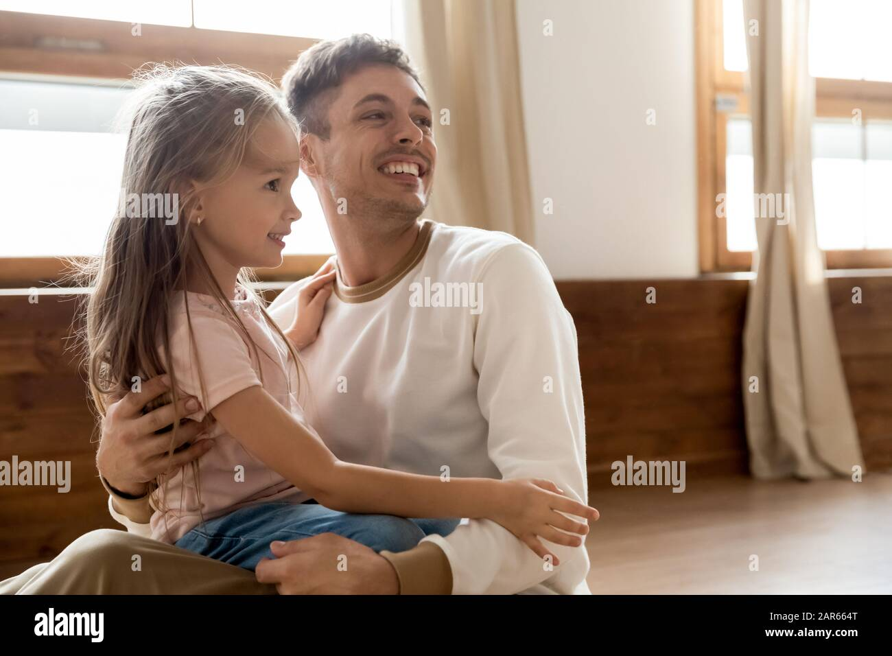 Smiling Young Dad Sit On Floor Play With Little Daughter Stock