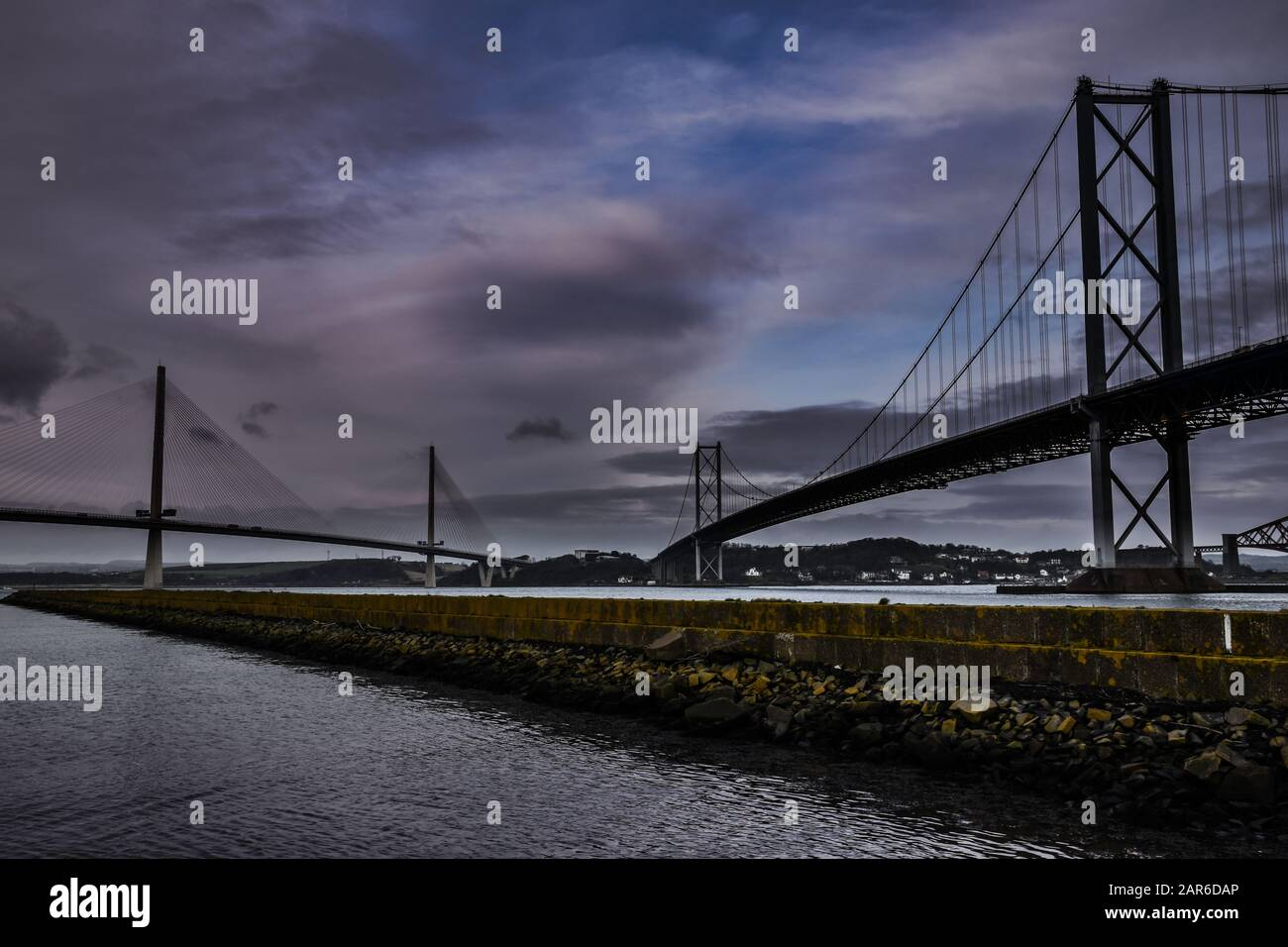 Forth Road Bridge and Queensferry Crossing bridges over the Forth Estuary in Scotland with dramatic skies, pier in foreground Stock Photo