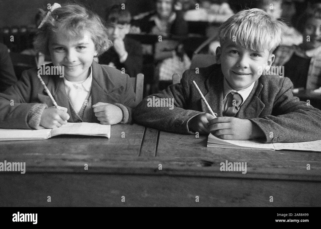 1955, historical, two young primary schoolchildren sitting beside each other at a wooden desk of the era in a classroom, eager to learn with their writing books open and pencils in hand, England, UK. Stock Photo