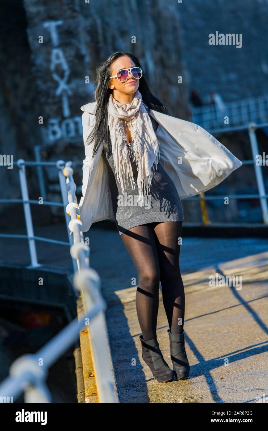 Full length wearing sunglasses Black tights sidelight sunshine sunlight standing on promenade near metal fence facing camera Winter warm clothing Stock Photo