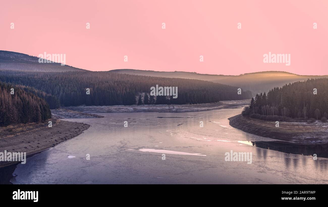 Frozen dam in the winter forest at sunset. A pink illuminated sky above Ecker Reservoir and Ecker Dam near Bad Harzburg, Harz mountain range, Germany. Stock Photo