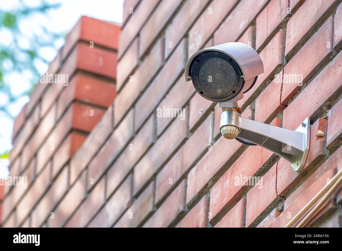 Surveillance camera on a red brick wall Stock Photo