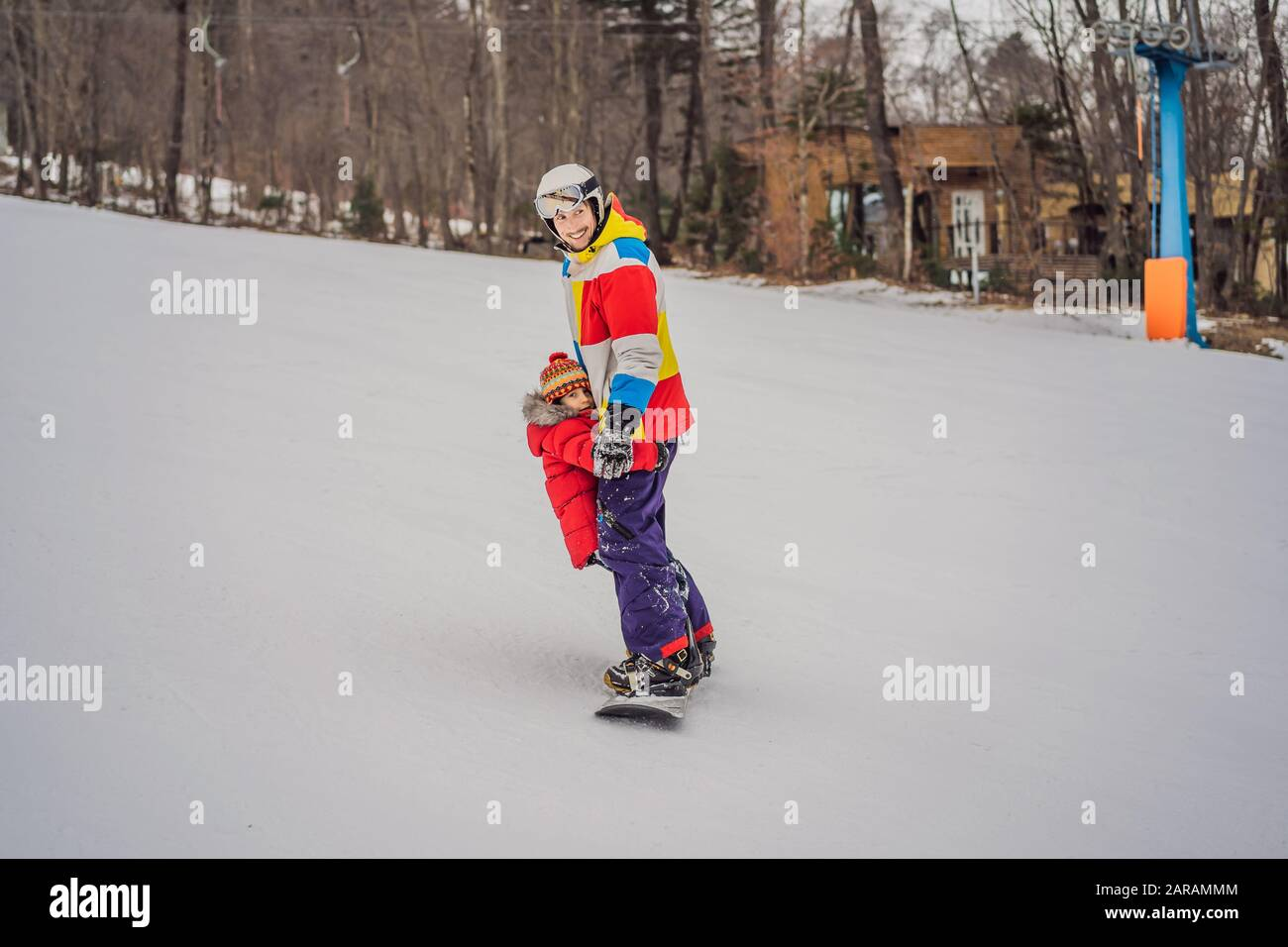 Dad and son ride the same snowboard, breaking safety precautions Stock Photo