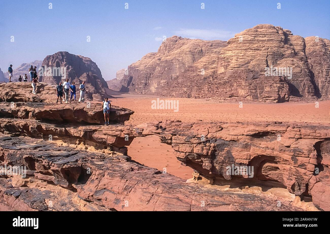 Jordan. Colourful desert mountain landscapes as tourists consider a walk of confidence across the rock arch of Al Kharza at the UNESCO World Heritage Site of Wadi Rum near the port of Aqaba in southern Jordan Stock Photo