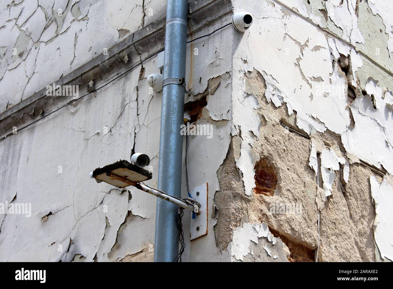Three new closed circuit TV CCTV security cameras mounted on corner of old abandoned building with dilapidated cracked facade next to new gutter pipe Stock Photo
