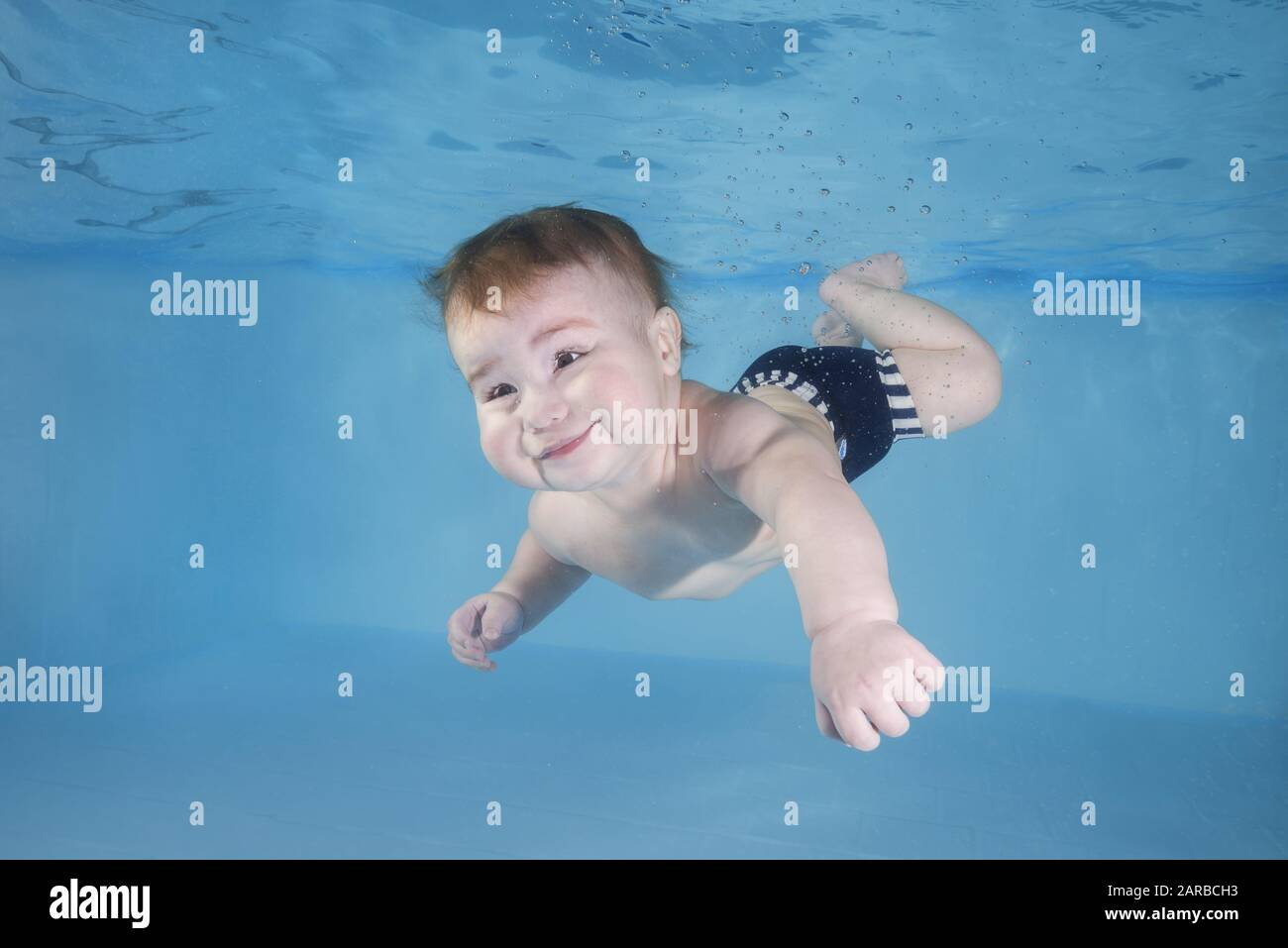 Little baby boy learns to swims underwater. Baby swimming underwater in the pool. Healthy family lifestyle and children water sports activity. Child d Stock Photo