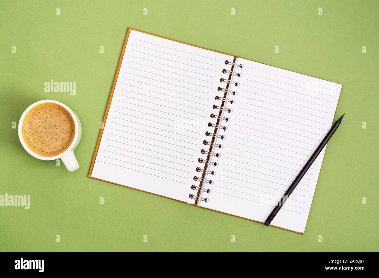 Open notebook with empty page and coffee cup. Table top, work space on green background. Creative flat lay. Stock Photo